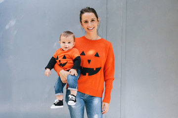 Mother and her baby dressed up as a pumpkin for Halloween.