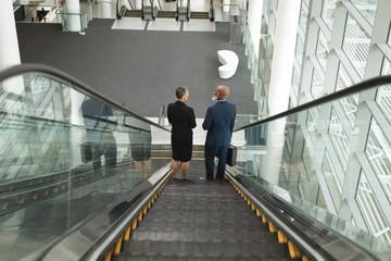 Businessman and businesswoman going down on an escalator