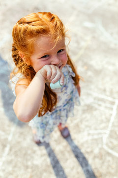Portrait of a smiling little redhead girl with colored chalks