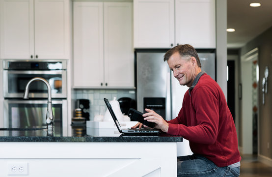 Home: Man Sits At Island With Laptop And Checks Phone
