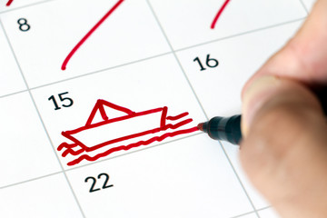 Human hand drawing a ship on the sea with a red pen in a white calendar.  Vacation concept