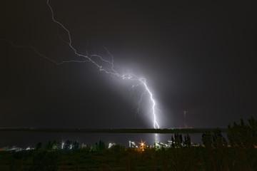 Bright flash of night lightning on the river bank.