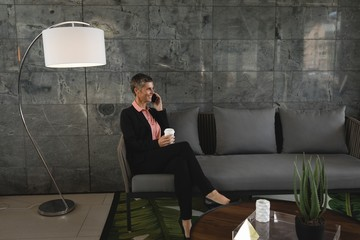Businesswoman sitting on the sofa and talking on the phone