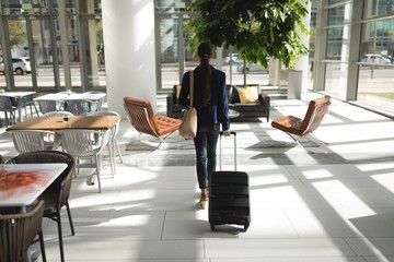 Businesswoman walking with suitcase in office