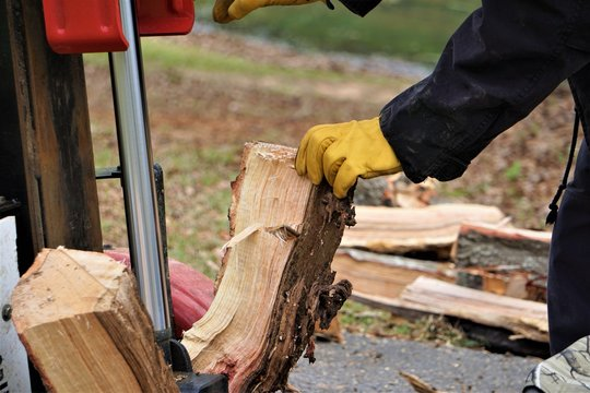 A man working with the firewood to split the logs by the machine on the driveway in the garden, Winter in GA USA.