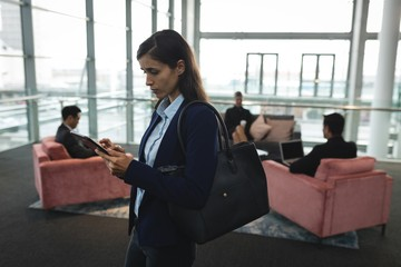 Businesswoman using her mobile phone in office