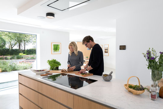 Couple preparing a meal on the countertop of their modern kitchen.