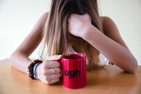 Female with a coffee mug that says ugh