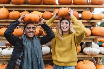 Two best friends in their twenties at a pumpkin patch Wall mural