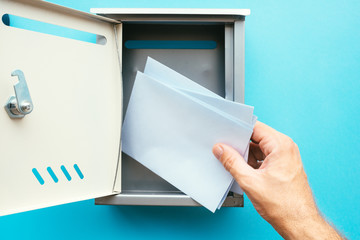 Hand inserting letter envelope into mailbox