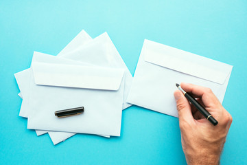 Hand writing address on blank white envelope