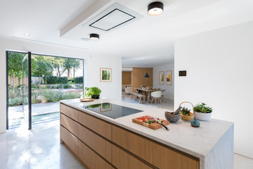 View of modern kitchen counter looking through to dining area. Glass exterior doors with views to the garden.