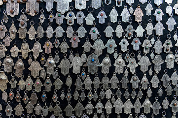Fatima hands jewelry assortment in a souk market