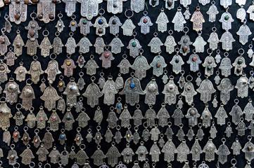 Fatima hands jewelry assortment in a souk market