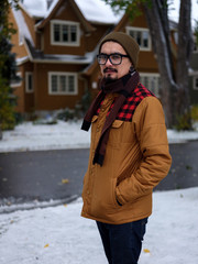 A portrait of a autumn-dressed man standing in front of a house that matches his jacket.