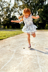 Portrait of a redhead little girl playing hopscotch