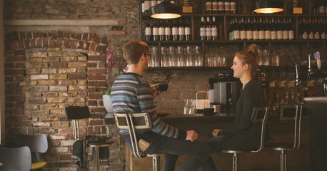 Couple having coffee while sitting at the bar counter