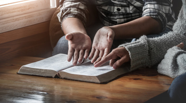 Two christianity sitting around wooden table with open holy bible and reading.