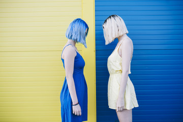 Two female friends standing in front of a blue yellow wall