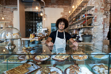 Handsome worker in bakery.