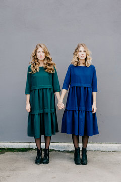 Twin women holding hands