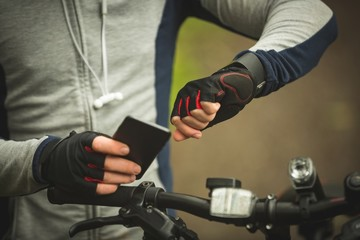 Mid section of cyclist checking time while using mobile phone