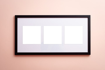 One blank canvas black border frame with three empty spaces on pink background on the wall