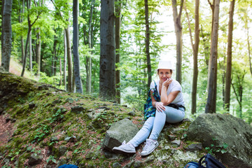 Woman sitting on a stone in forest during adventures