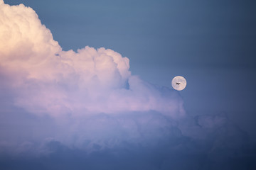 Airplane silhouette crossing the moon by a cloudy night sky