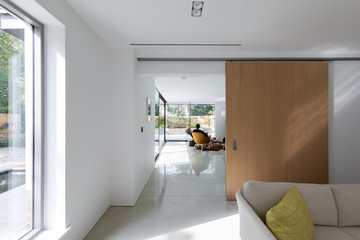 View through the living room of a modern house to a garden room with couple.
