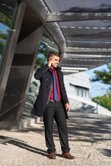 Happy successful freelance manager answering call while walking over city. Cheerful handsome young man in coat talking on phone and standing near modern building. Mobility concept