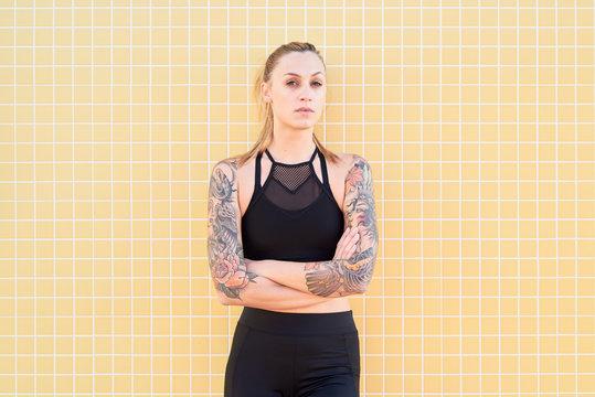 Sportswoman with tattooed arms in sportswear.