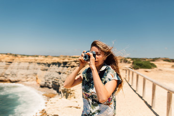 Young woman taking pictures near to Atlantic coast