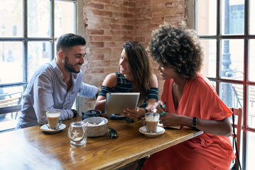 Group of three stylish friends posing at table with coffee cups and watching tablet together.