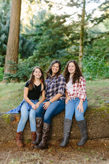 Mother and Daughters Sitting on Log for Portrait