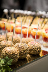 Close-up of Chocolate and Nut Covered Apples and Glasses of Fruit Cocktail on Dessert Table