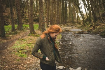Woman looking at river in forest