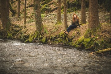 Young female hiker sitting near river coast in the forest