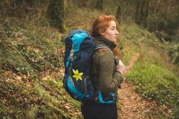 Female hiker with backpack looking around in the forest