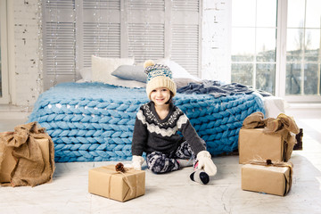 little baby girl is folding up a mountain of gift boxes at home, near the bed. The interior is decorated with Christmas decor. Daytime bright sunlight from the window. New Year theme