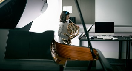 Schoolgirl playing french horn in music school