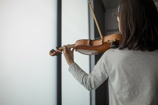 Schoolgirl playing violin in music school