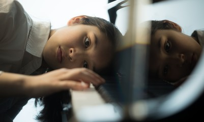 Schoolgirl playing piano in music school