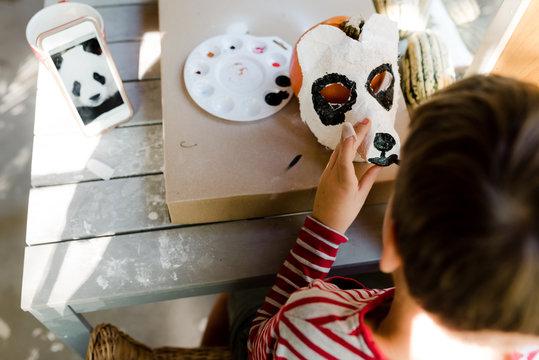 little boy making  a plaster panda bear mask