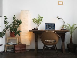 Office with wooden desk and laptop