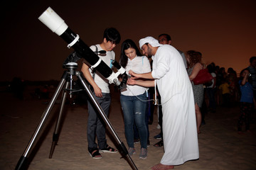 "An Emirati man uses a telescope to take a picture of the lunar eclipse of a full ""Blood Moon"" at Al Sadeem Observatory in Al Wathba near Abu Dhabi"