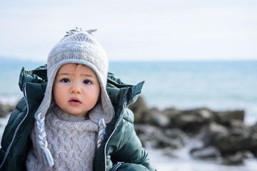 Baby boy in hat and jacket by sea in Winter, Italy