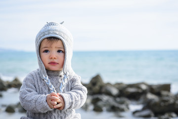 Baby boy in hat and sweater by sea in Winter, Italy