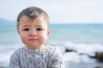 Portrait of baby boy in sweater by sea