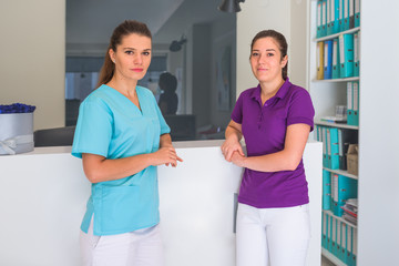 Portrait of female orthodontist accompanied by her assistant